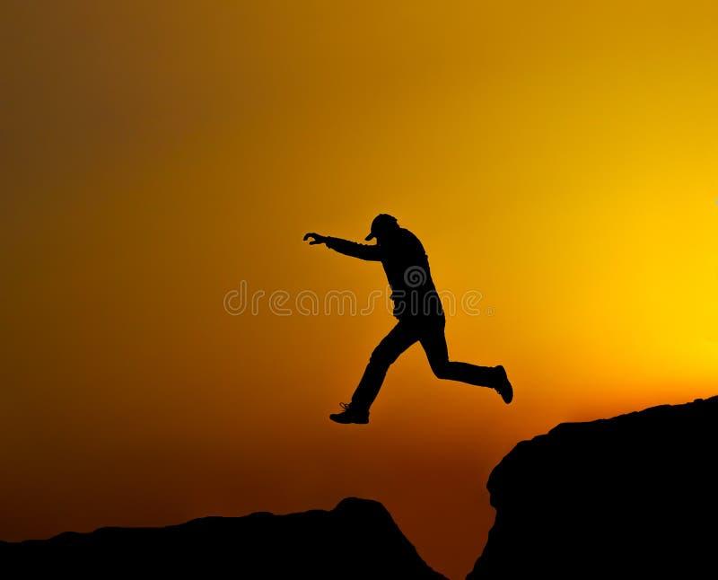 Человек силуэта скачет стоковая фотография rf