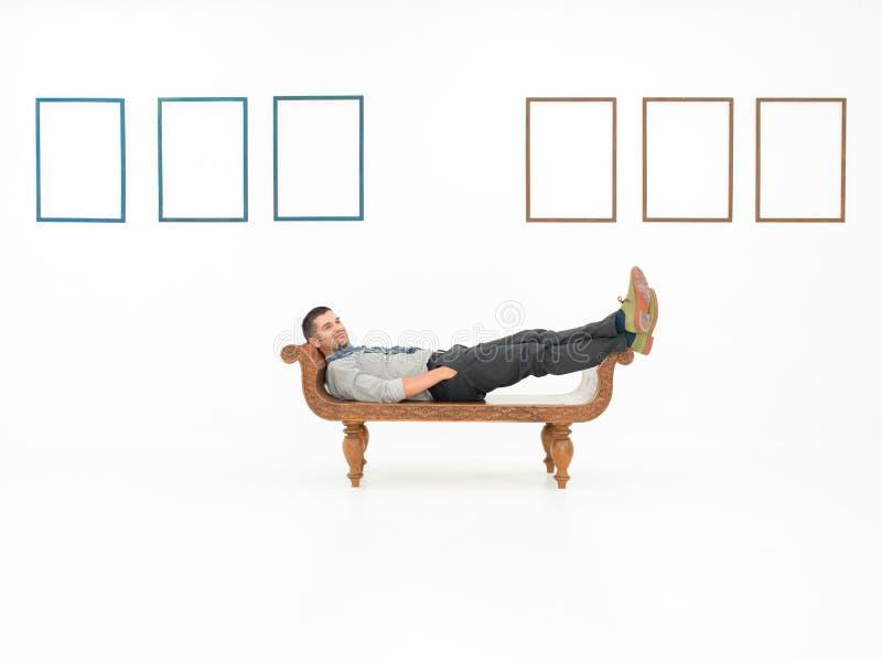 Человек сидя в художественной галерее с пустыми рамками стоковая фотография rf