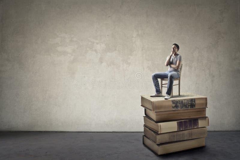 Человек сидя на книгах стоковые изображения rf
