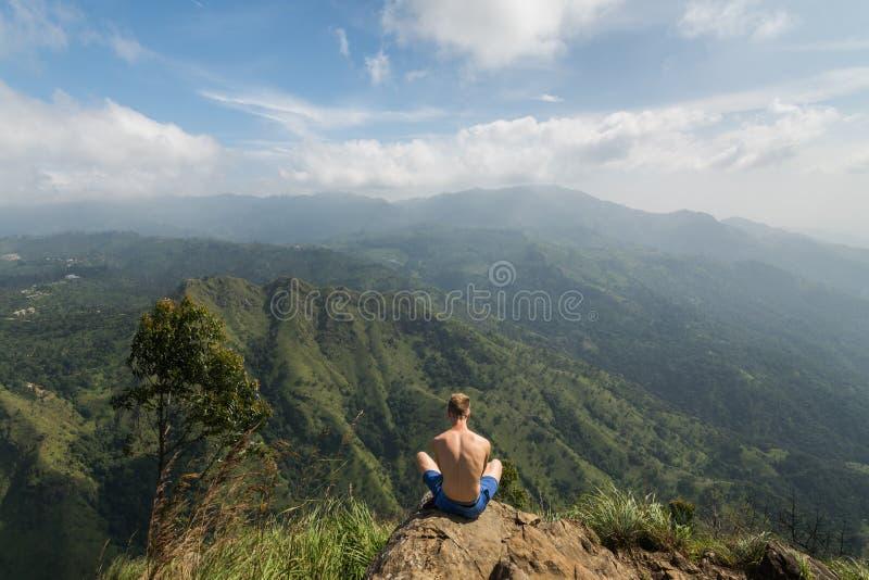 Человек сидя на крае пика маленького Адама стоковые изображения