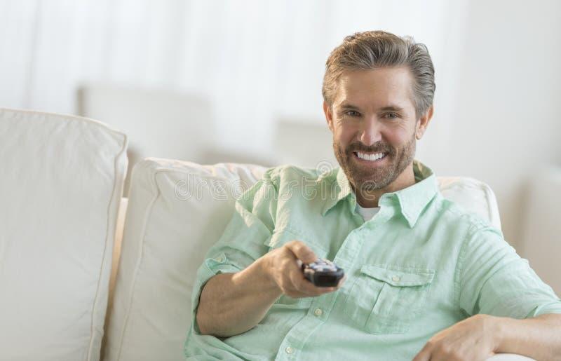 Человек сидя на софе с дистанционным управлением стоковая фотография rf