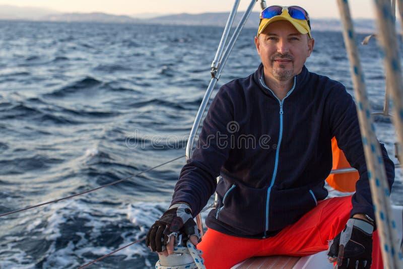 Человек сидя на яхте плавания на море стоковые изображения rf