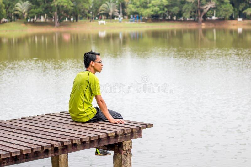 Человек сидя около озера стоковые фотографии rf