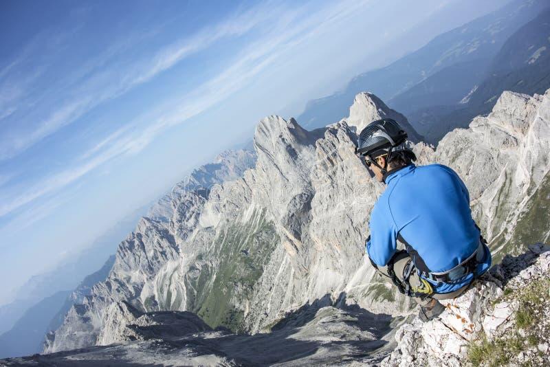Человек сидя na górze горы стоковая фотография rf