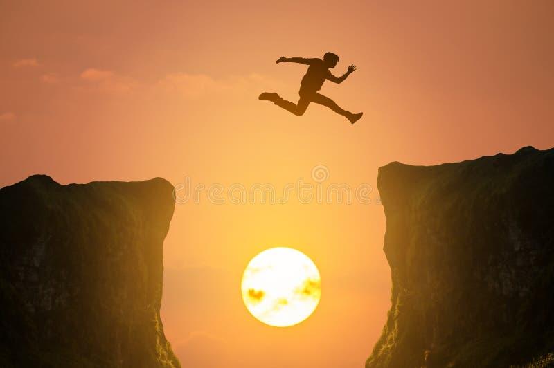Человек скача над скалой, силуэт стоковое изображение