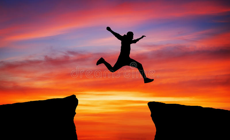 Человек скача через зазор стоковое фото