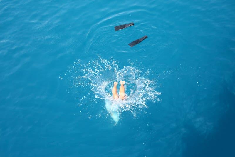 Человек скачет в воду с брызгает и флипперы стоковое фото