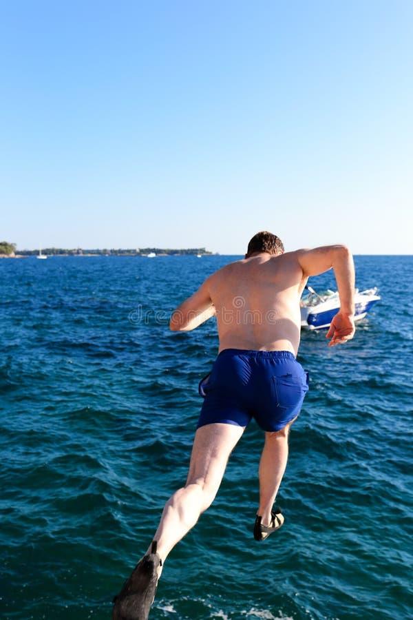 Человек скачет в океан стоковое изображение