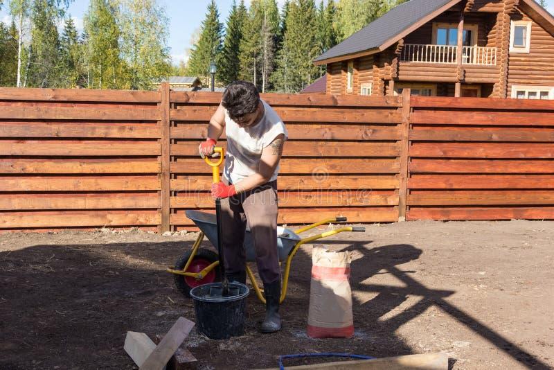 Человек смешивает цемент с лопаткоулавливателем в ведре стоковые изображения