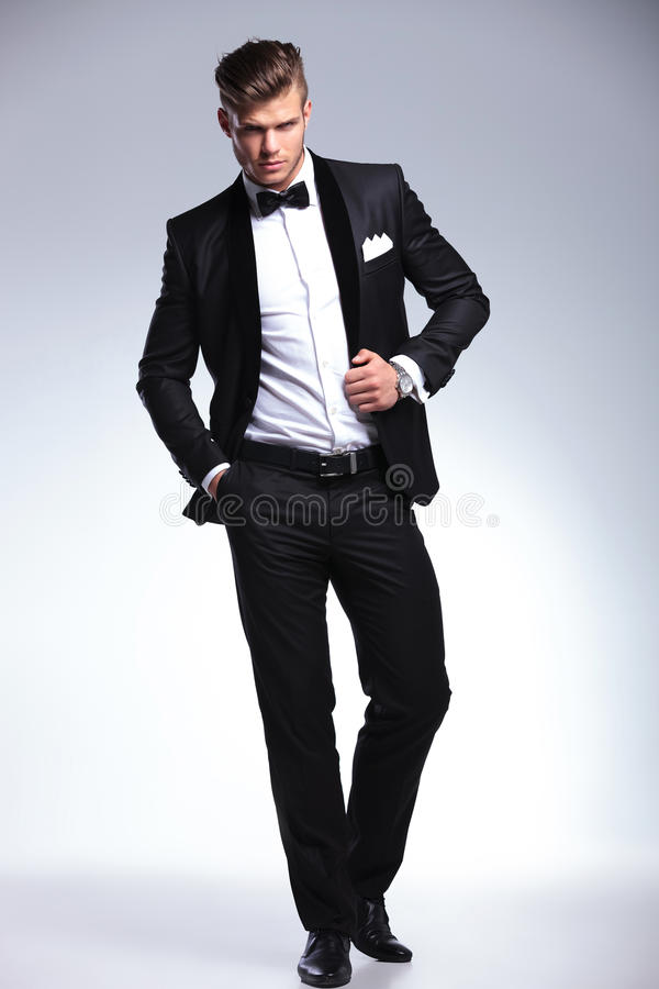 Человек смокинга представляет с рукой на куртке и в карманн стоковое фото