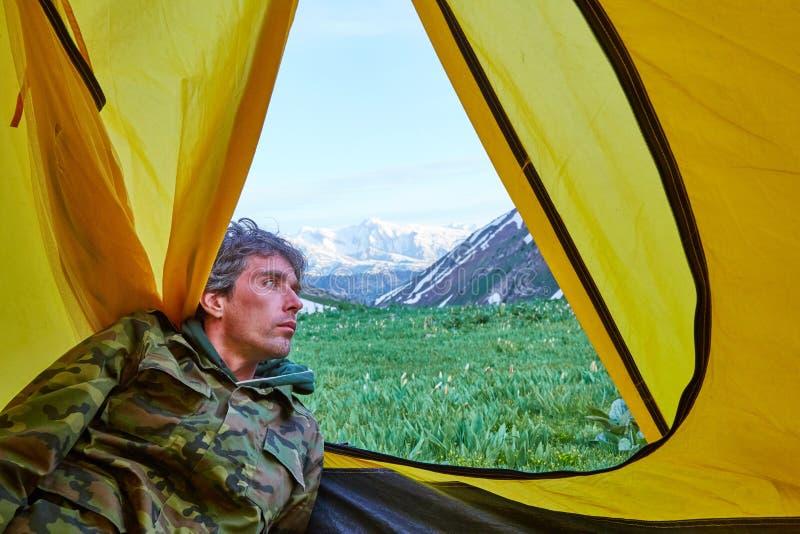Человек смотрит от шатра на горах стоковое изображение