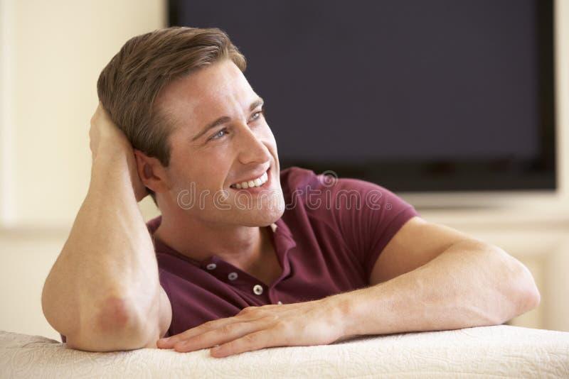 Человек смотря широкоэкранное ТВ дома стоковая фотография rf