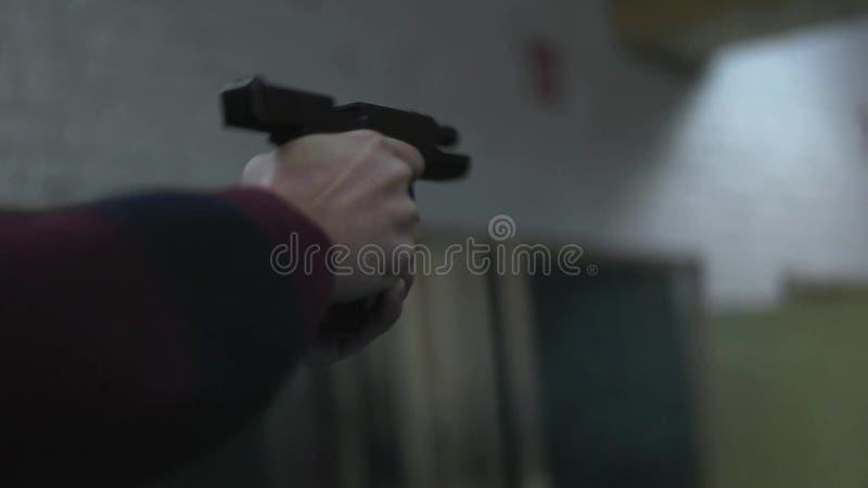 Человек снимает оружие на конце стрельбища вверх видеоматериал