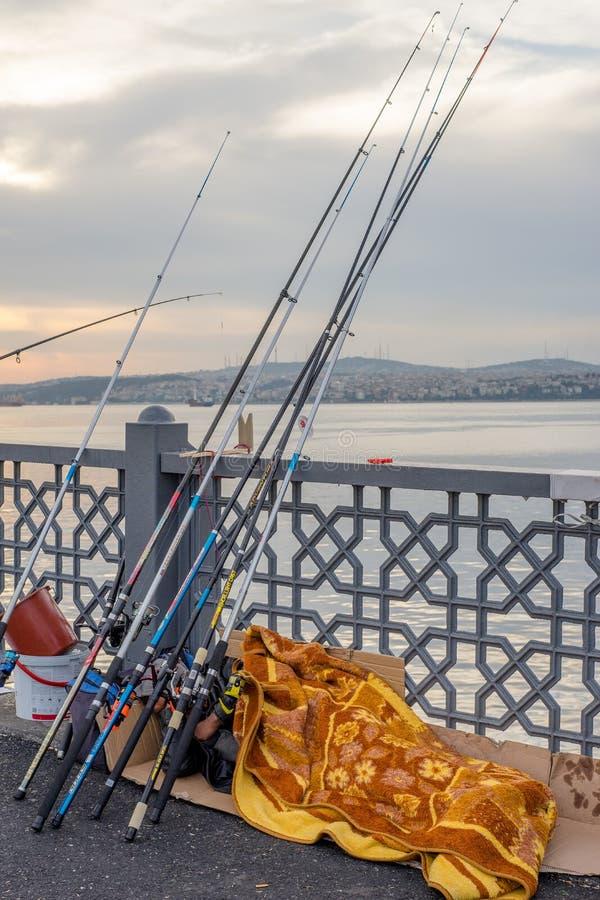 Человек спать под много рыболовных удочек в одеяле на мосте Galata стоковые фото