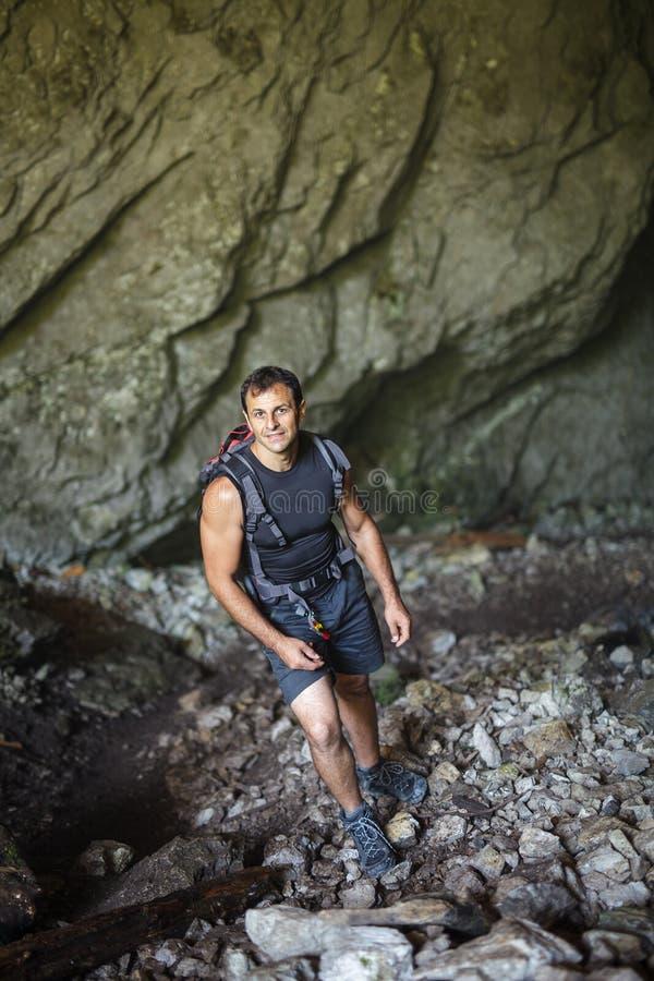 Человек стоя внутри пещеры стоковое изображение