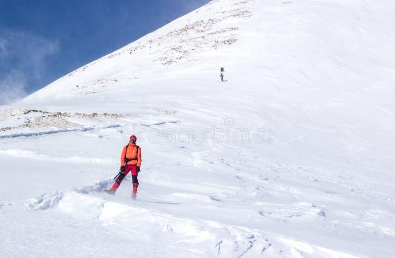 Человек стоя в идти снег наклоне стоковые изображения rf
