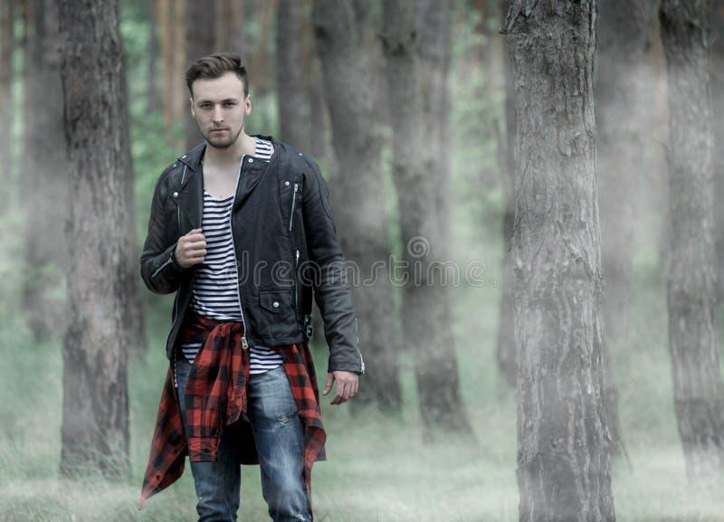 Человек стоя в туманном лесе стоковые фото