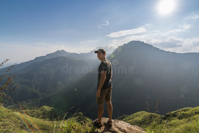 Человек стоя на крае пика маленького Адама стоковая фотография