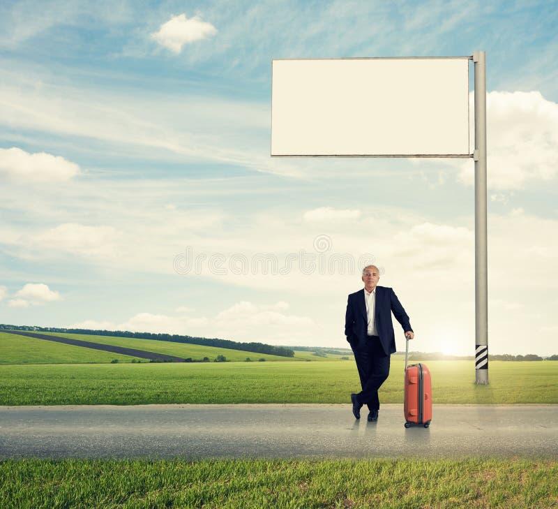 Человек стоя против белой пустой афиши стоковые фотографии rf