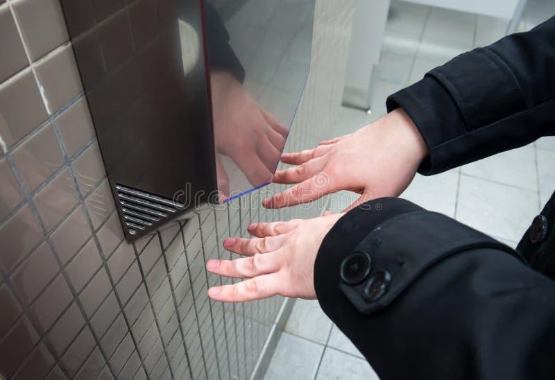 Человек сушит влажные руки с сушильщиками электрическими руки стоковое изображение