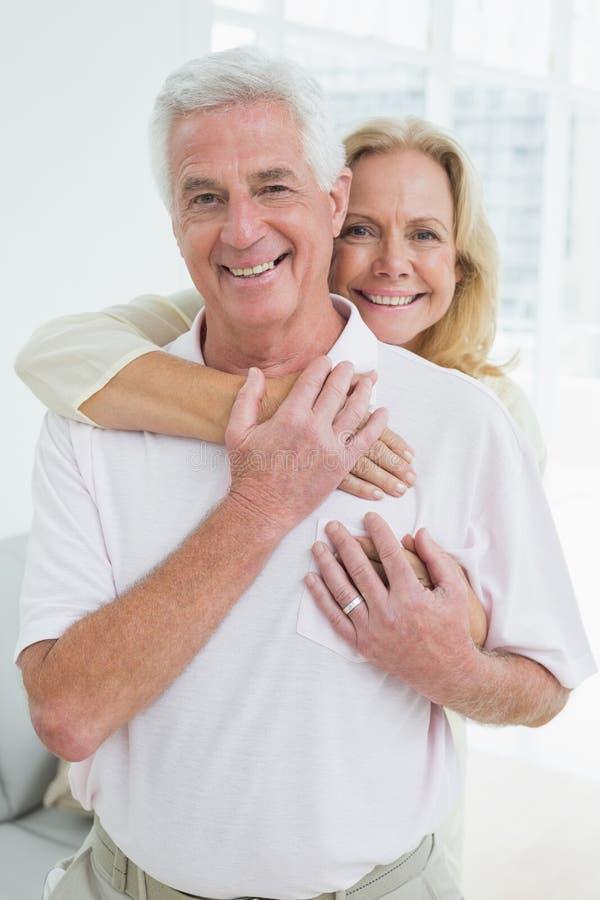 Человек счастливой старшей женщины обнимая от позади стоковое изображение rf