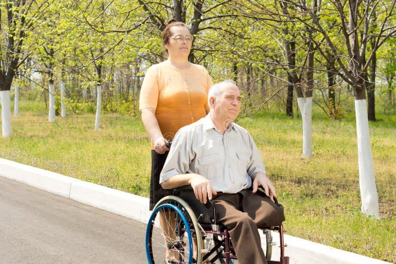 Человек с ампутированной конечностью будучи приниманным для прогулки в кресло-коляске стоковое фото
