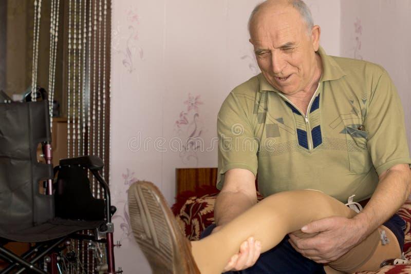 Человек с ампутированной конечностью смотря его новую простетическую ногу стоковое изображение