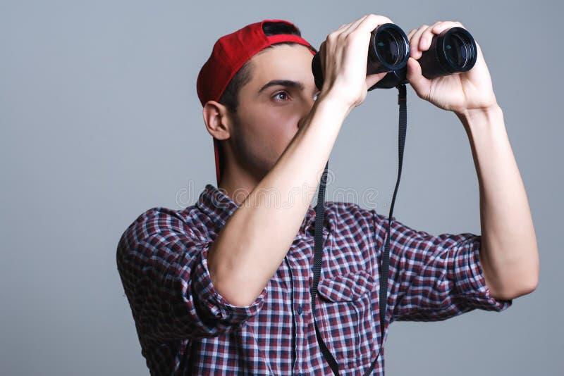 Человек с биноклями в студии на серой предпосылке стоковые изображения rf