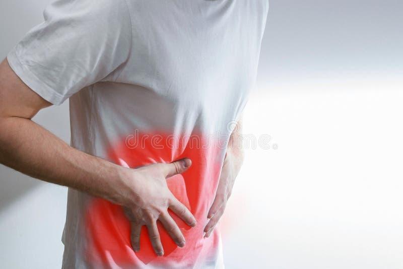 Человек с болью в животе, болью, вопросами, в белой рубашке, на белизне стоковая фотография