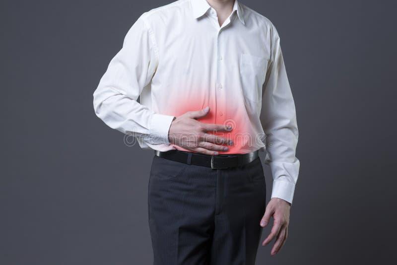 Человек с болью в животе, болью в животе на серой предпосылке стоковые фотографии rf