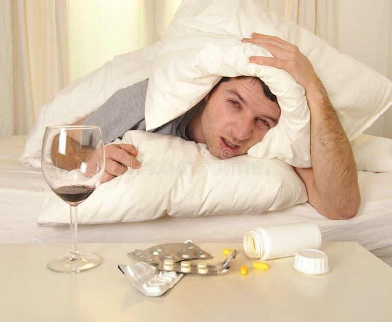 Человек с головной болью и похмельем в кровати с таблетками стоковая фотография rf