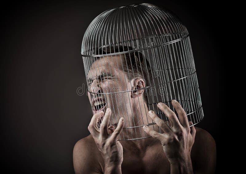 Человек с головой внутри birdcage стоковая фотография rf