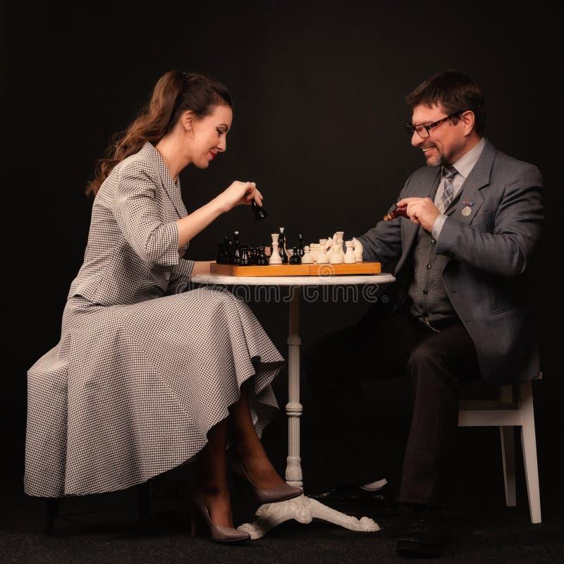 Человек с девушкой играет шахмат и курит трубу на темном backgr стоковое изображение