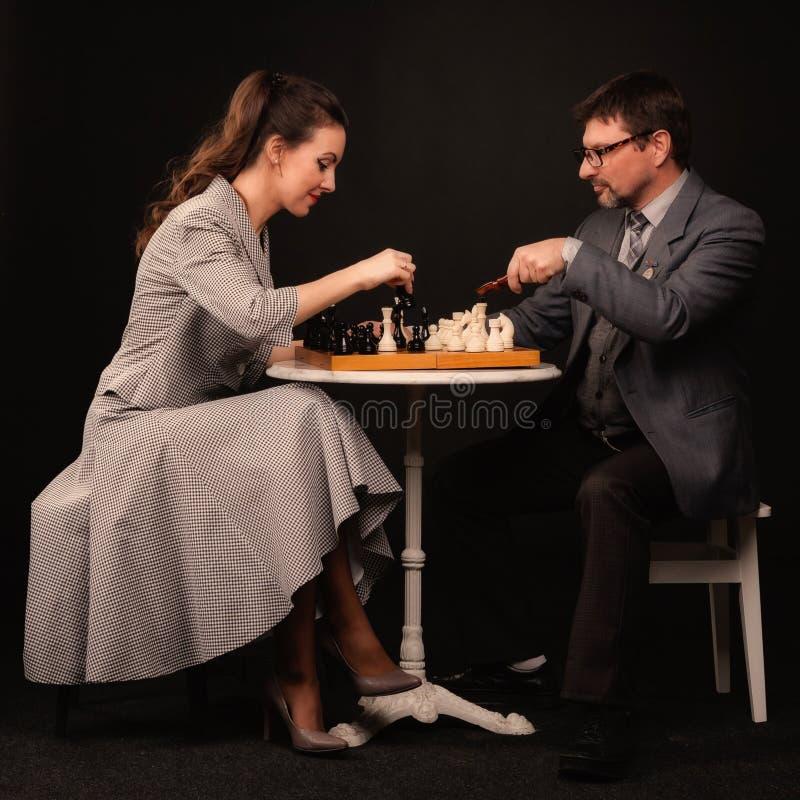 Человек с девушкой играет шахмат и курит трубу на темном backgr стоковое фото