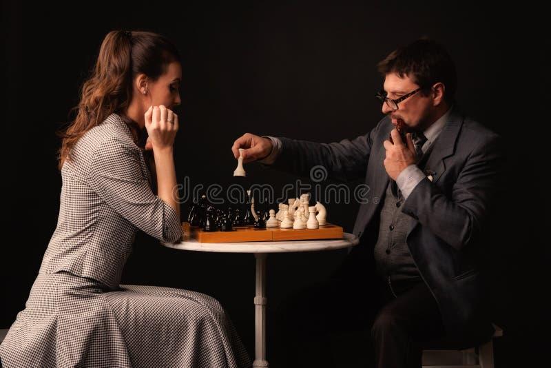 Человек с девушкой играет шахмат и курит трубу на темном backgr стоковые изображения