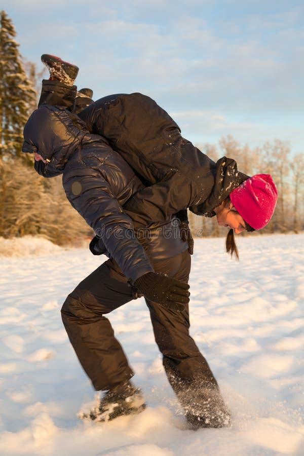 Человек с девушкой на плечах в зиме стоковая фотография