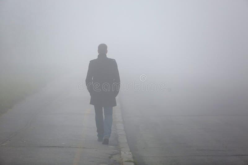 Человек с его задняя часть идя через улицу тумана стоковые изображения rf