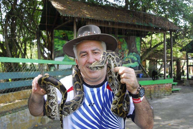 Человек с змейкой вокруг его шеи стоковое фото