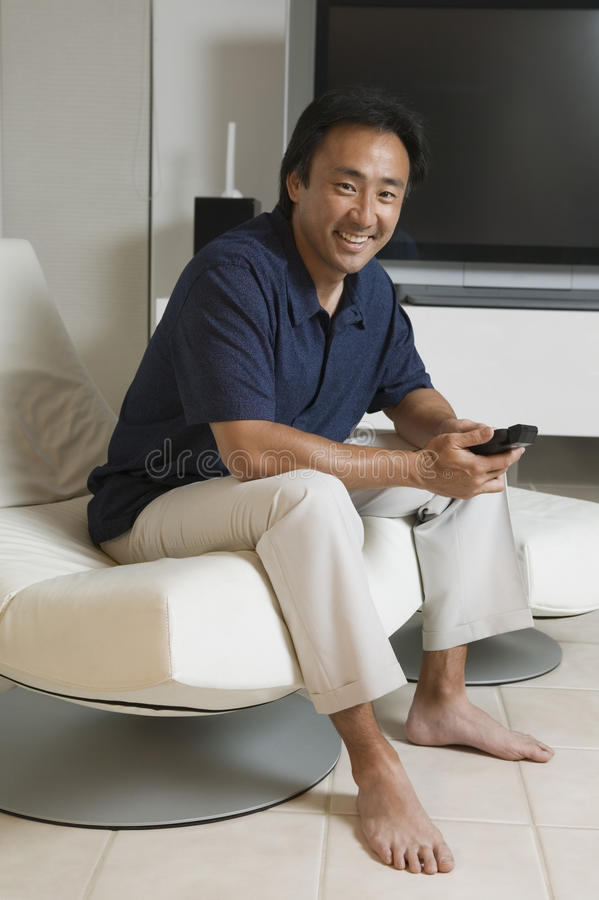 Человек с дистанционным управлением перед большим экраном ТВ дома стоковая фотография rf