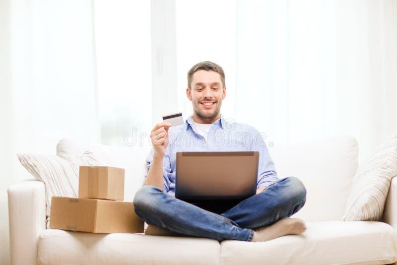 Человек с компьтер-книжкой, кредитной карточкой и картонными коробками стоковое фото