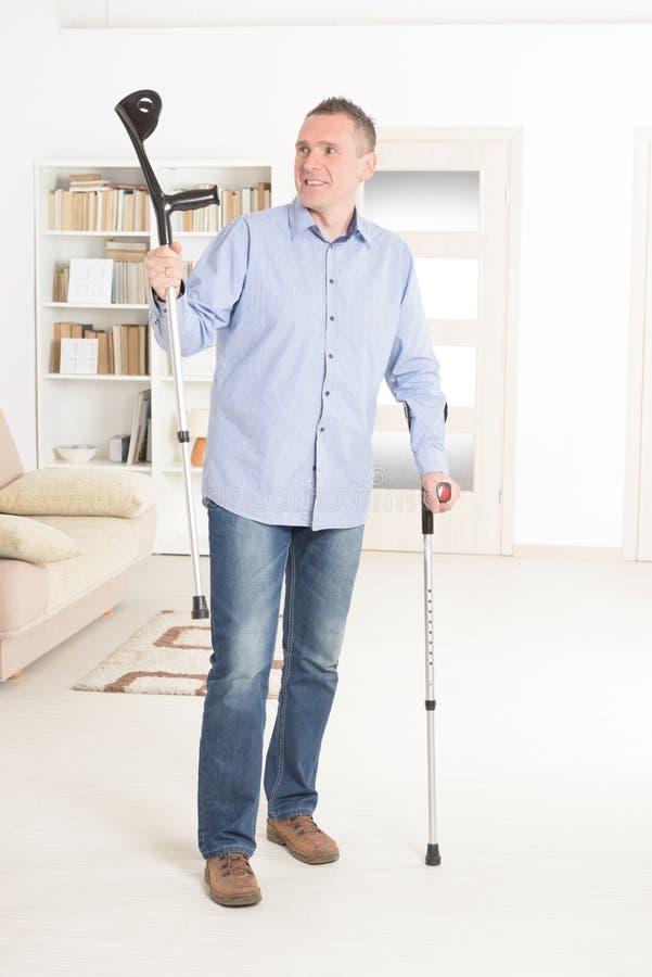Человек с костылями стоковая фотография rf