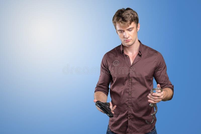 Человек с оружием и наручниками стоковое фото