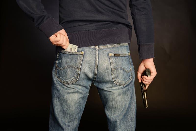 Человек с оружием получает деньги от его карманн стоковая фотография