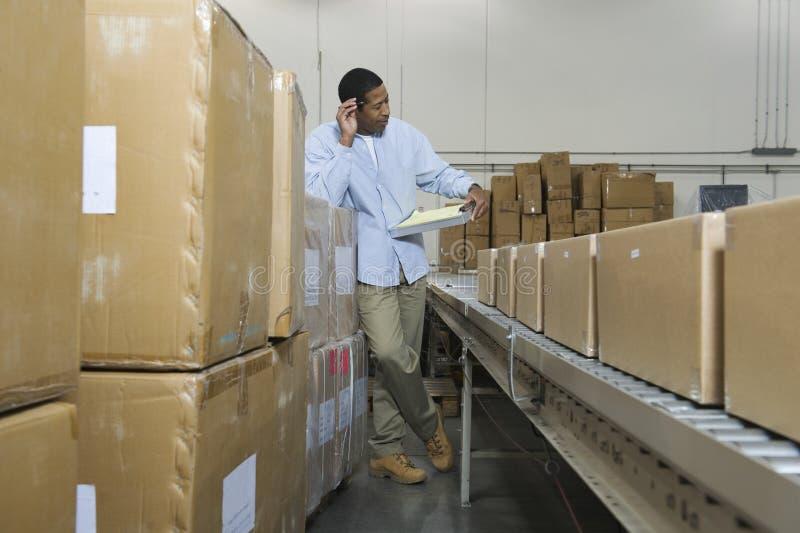 Человек с доской сзажимом для бумаги конвейерной лентой и коробками в складе стоковое изображение