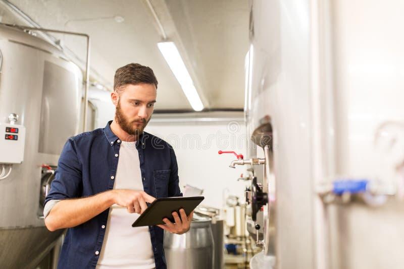 Человек с ПК таблетки на винзаводе ремесла или заводе пива стоковое фото