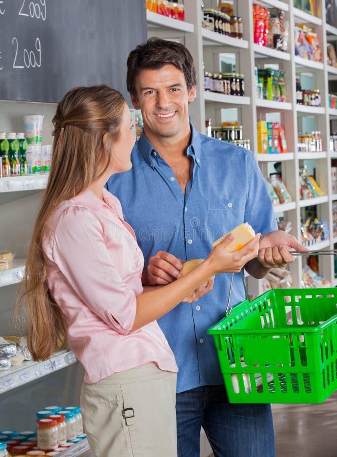 Человек с покупками женщины в гастрономе стоковые изображения