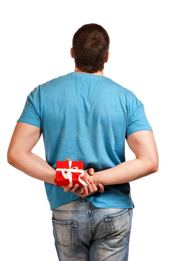 Человек с подарком в руке. Взгляд от задней части. стоковые фото