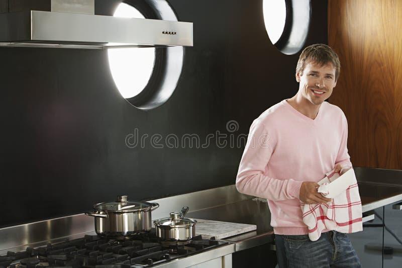Человек с полотенцем для чайной посуды в кухне стоковые фото