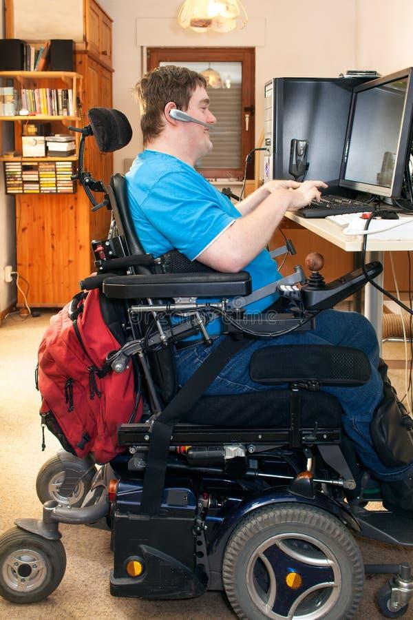 Человек с ребячьим церебральным параличом используя компьютер стоковая фотография