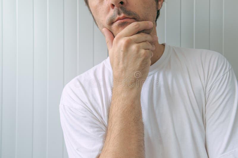 Человек с рукой на подбородке думая глубокие мысли стоковые фотографии rf